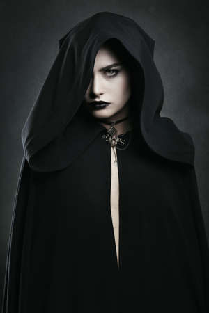 Beautiful vampire woman with black cloak . Halloween and horror Stock Photo