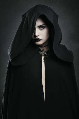 Mooie vampier vrouw met zwarte mantel. Halloween en horror Stockfoto