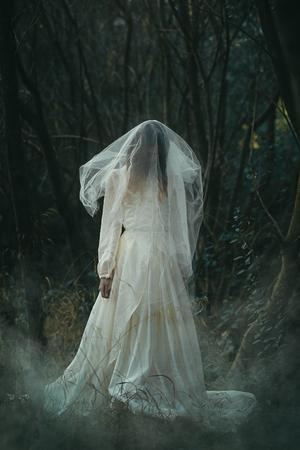 mist: Creepy lone bride in misty woods . Halloween conceptual