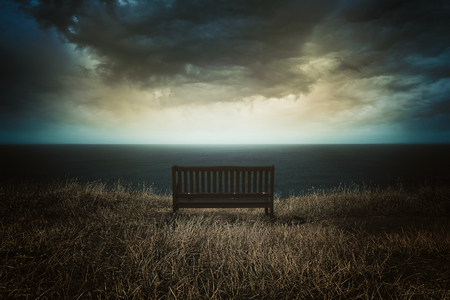 dark skies: Bench in front of a dramatic cloudscape . Surreal sky Stock Photo