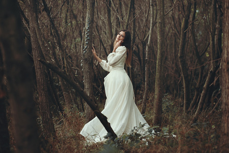 the innocence: Romantic beautiful woman posing in autumn woods . Innocence and purity
