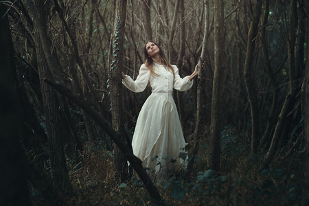 innocence: Young romantic woman in desolate autumn forest . Innocence and loneliness
