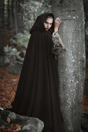 Forest keeper with black cloak and grey owl. Fantasy and legend Stok Fotoğraf