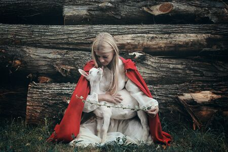 Young woman and her little goat. Friendship and love Standard-Bild