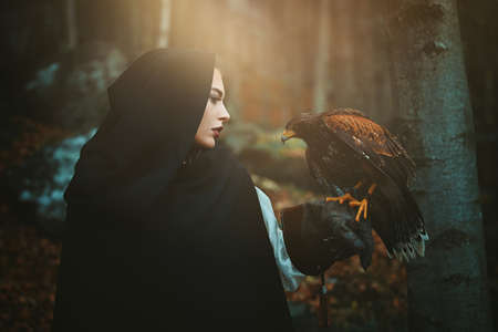 Dark hooded woman and hawk. Cinematic colors portrait outdoor