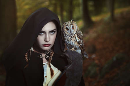 Dark hood woman with owl on her shoulder. Fantasy shot