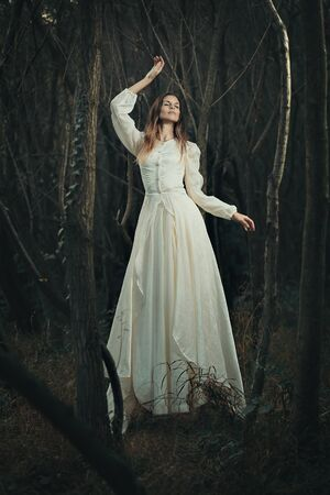 realm: Victorian dressed woman levitation . Surreal and ethereal Stock Photo