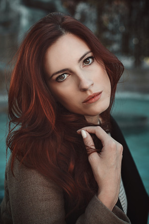 Beautiful emotive portrait of red haired woman . Seasonal and autumn