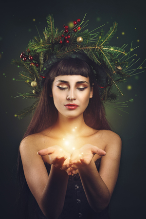 jule: Beautiful girl with christmas crown and magic dust Stock Photo