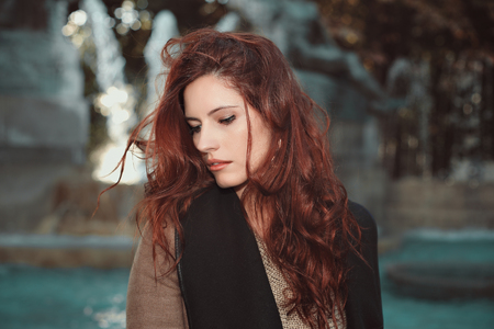 Beautiful young woman with red hair . Fountain background