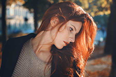 Autumn portrait of a beautiful red haired woman. City and urban Standard-Bild