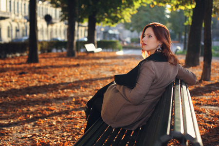 Beautiful red haired woman on a bench at the park