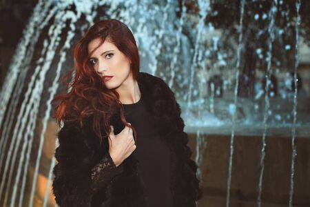 Beautiful fashion model with red hair. Urban shot