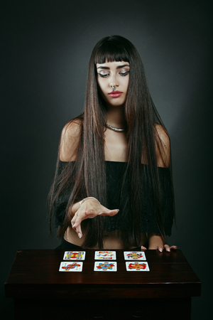 soothsayer: Beautiful fortune teller with tarot cards . Mistery and cartomancy