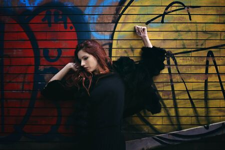 Red haired woman against wall painting . Urban fashion