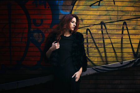 Fashion woman against wall painting background Street and urban
