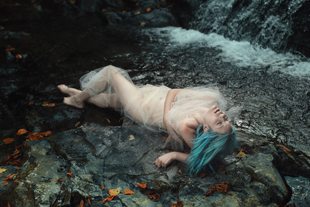 sea nymph: Beautiful cyan haired mermaid on rocks. Fantasy and fairytale Stock Photo