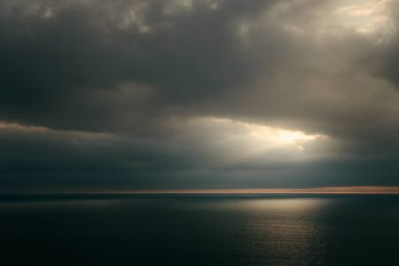 Dramatic sunset over green sea. Dark cloudscape