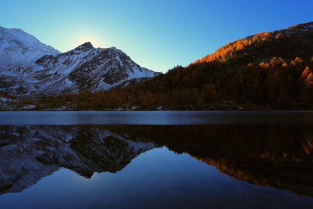 Arpy lake waters at dusk . Alpine mountains reflection