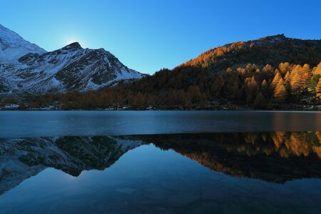 Blue Arpy lake at dusk with autumn trees. Alpine mountains reflection  Standard-Bild