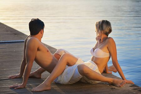 caresses: Intimate couple looking at sunset on a pier. Romance Stock Photo