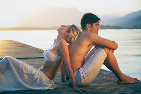 caresses: Couple enjoying sunset light on a pier.Love and sharing