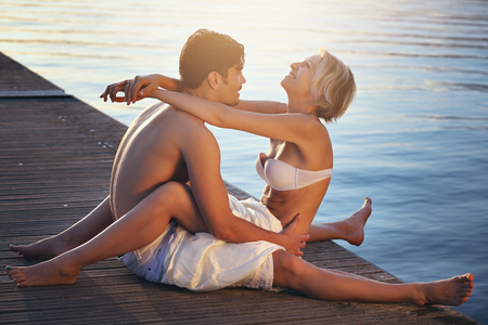 caresses: Happy couple on sea pier. Holiday relax