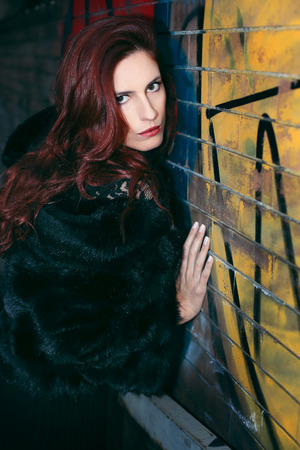 Red haired woman posing against graffiti. Street fashion Standard-Bild