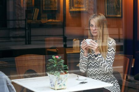 Woman with a cup of coffee. Urban shot through the window