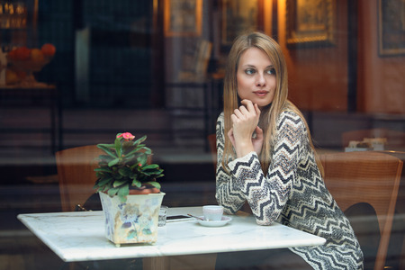 Young woman taking a break in elegant cafe. Urban lifestyle