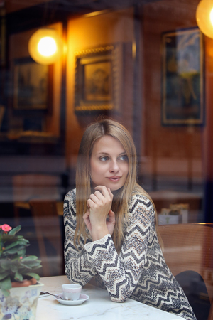 Woman waiting inside an elegant cafe. Urban lifestyle