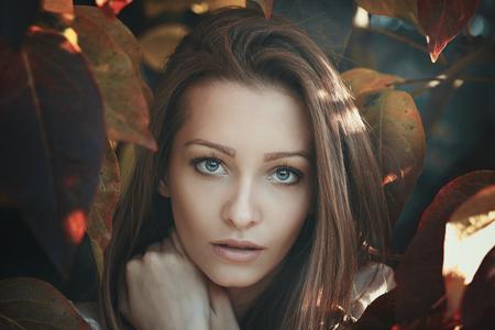 color tone: Beautiful young woman gaze . Autumn leaves portrait