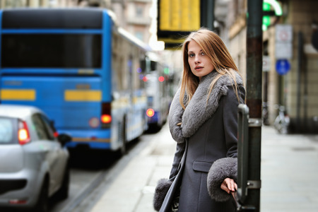 Street portrait of a woman at bus stop. Urban background Standard-Bild