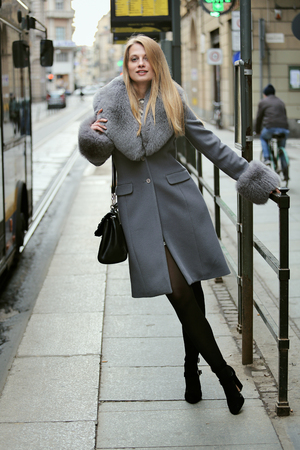 Beautiful stylish woman at the tram stop. Urban lifestyle Standard-Bild