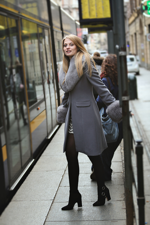 fashionable woman: Fashion woman waiting the tram. Urban lifestyle