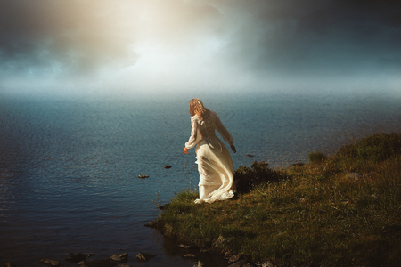 photomanipulation: Woman looking at surreal waters. Photomanipulation with dreamy colors Stock Photo