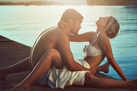 caresses: Happy couple relaxing on sea pier. Holiday
