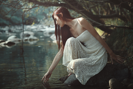 Thoughtful woman touching stream waters. Forest light