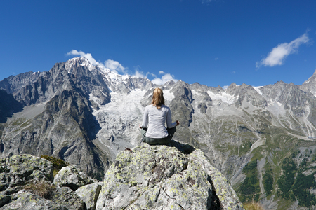 Young woman relaxing in front of Mont Blanc, Courmayeur, Italy