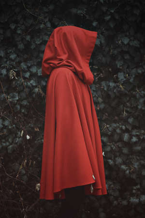 Dark portrait of red hooded person. Ivy background