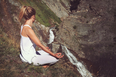 Woman in yoga positiion looks at waterfall. Meditation and relax Standard-Bild