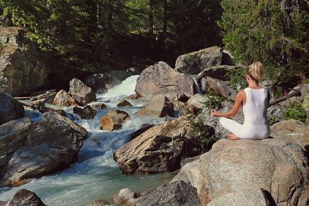 Woman meditation near a mountain stream Standard-Bild