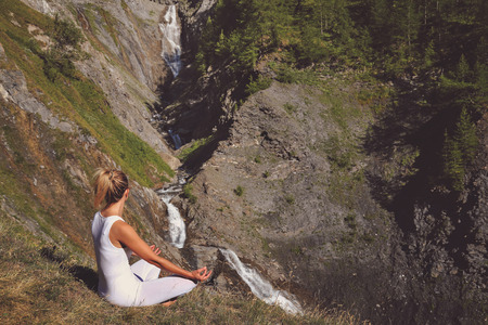Woman meditation close to a waterfall. Nature relaxation