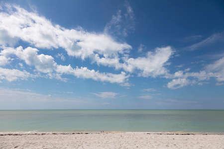 Typical coast of Sanibel Island, sand, water, birds, blue sky and clouds, Florida, USA Banco de Imagens