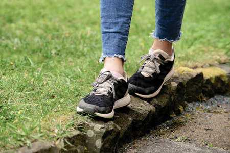 A lady is jogging on narrow path after wearing new shoes Foto de archivo