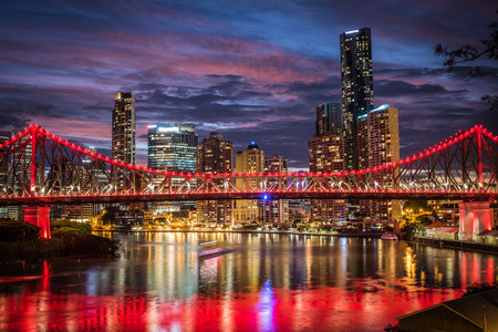 storey: Pink sunset behind the red lights of the Storey Bridge against the Brisbane city skyline
