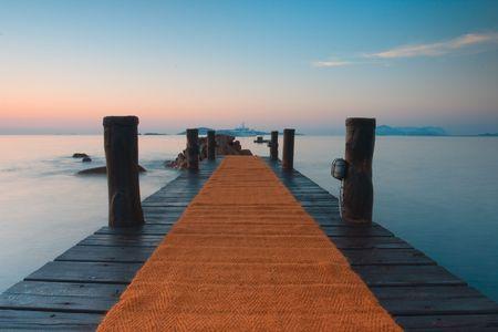 Wooden jetty on beautiful Romazzino beach on Sardinia in italy 免版税图像