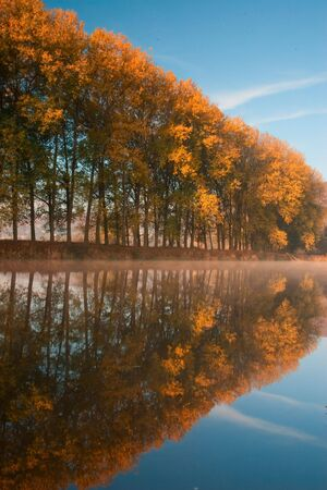 Reflection on the river at sunset in autumn photo