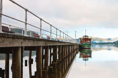 Scenic view of boats moored by wooden pier , Lake District National Park, England. photo
