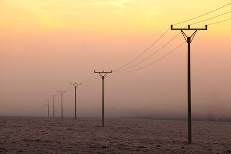 Power-transmission poles in the mist in winter nature photo